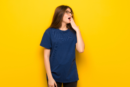 Young woman with glasses over yellow wall yawning and covering wide open mouth with hand Stock Photo