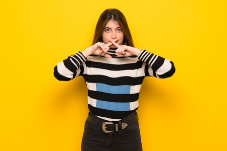 Young woman over yellow wall showing a sign of silence gesture