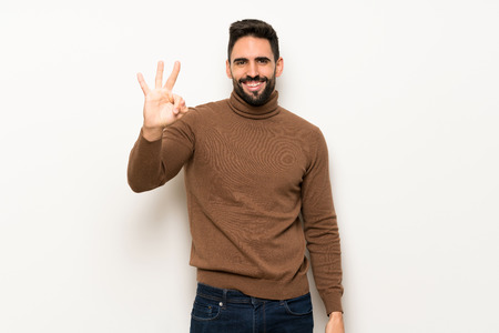 Handsome man over white wall happy and counting three with fingers Stock Photo