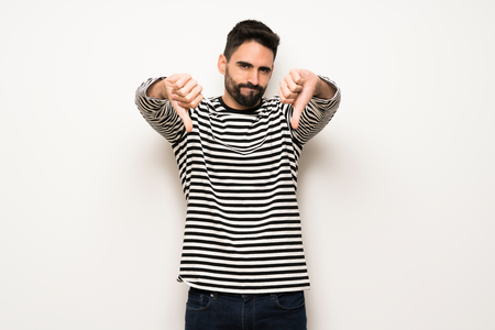 handsome man with striped shirt showing thumb down with both hands