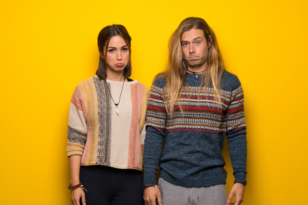 Hippie couple over yellow background with sad and depressed expression