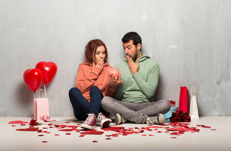 Couple in valentine day surprised while holding a piggybank