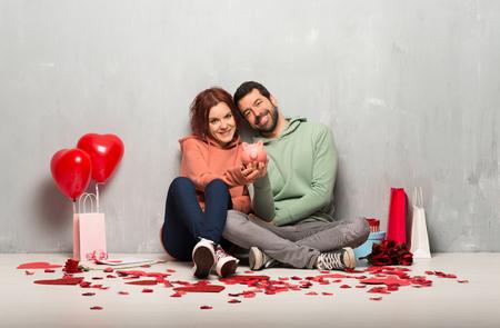 Couple in valentine day holding a piggybank Reklamní fotografie