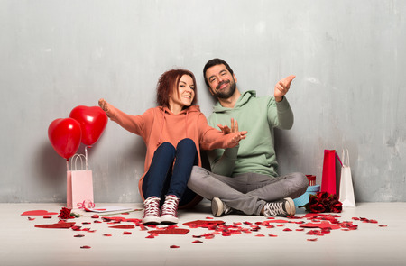 Couple in valentine day presenting and inviting to come