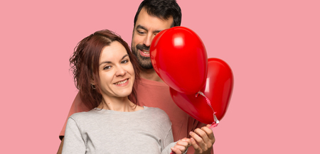Couple in valentine day with balloons with heart shape over isolated pink background