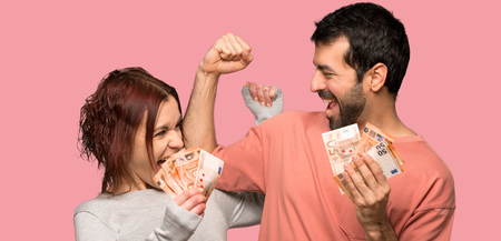 Couple in valentine day taking a lot of money over isolated pink background