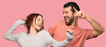 Couple in valentine day enjoy dancing while listening to music at a party over isolated pink background Stock Photo