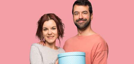 Couple in valentine day holding a gift in hands over isolated pink background