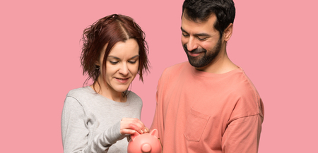 Couple in valentine day taking a piggy bank over isolated pink background