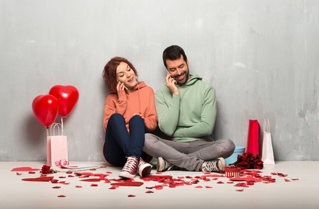 Couple in valentine day keeping a conversation with the mobile phone