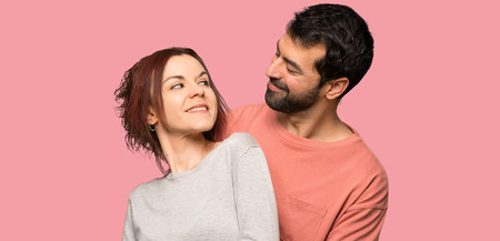 Couple in valentine day hugging over isolated pink background