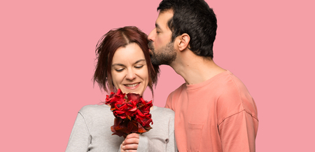 Couple in valentine day with flowers over isolated pink background Stock Photo