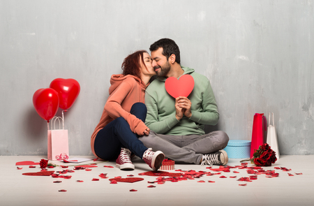 Couple in valentine day holding a heart symbol and kissing Stock Photo