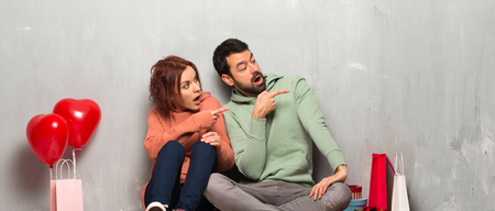 Couple in valentine day pointing finger to the side with a surprised face