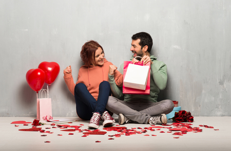 Couple in valentine day holding shopping bags in victory position Stock Photo