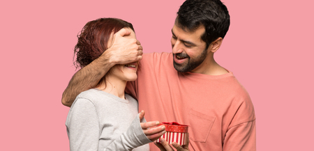 Couple in valentine day holding gift box over isolated pink background