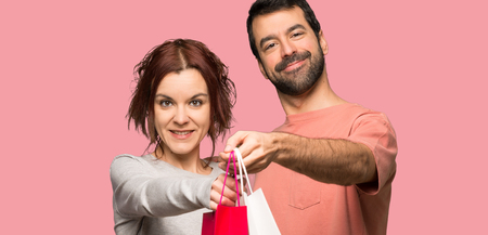 Couple in valentine day holding a lot of shopping bags over isolated pink background