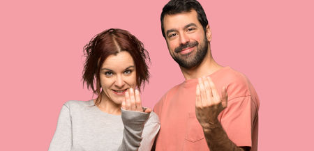 Couple in valentine day inviting to come with hand over isolated pink background