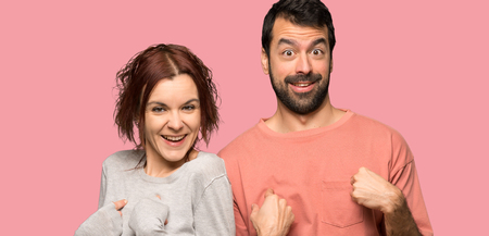 Couple in valentine day with surprise facial expression over isolated pink background