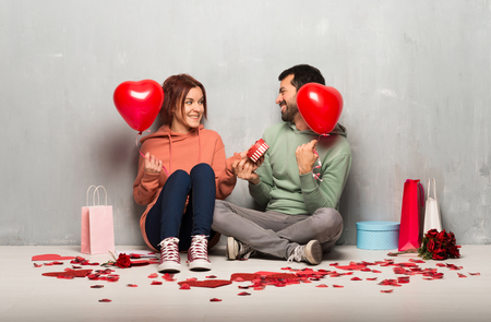 Couple in valentine day holding a heart symbol and balloons