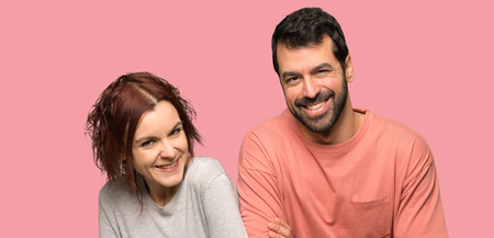 Couple in valentine day keeping the arms crossed while smiling over isolated pink background