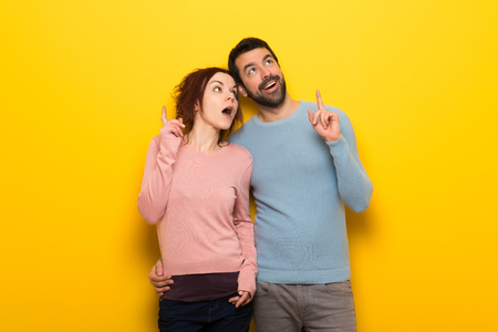 Couple in valentine day thinking an idea pointing the finger up
