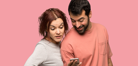 Couple in valentine day sending a message with the mobile over isolated pink background