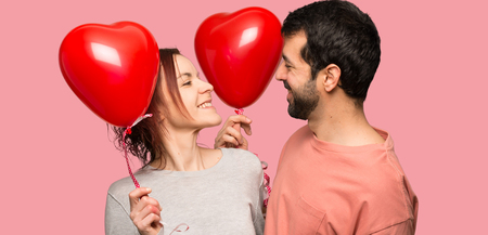 Couple in valentine day holding a heart symbol and balloons over isolated pink background