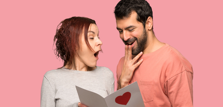 Couple in valentine day with valentines day card over isolated pink background