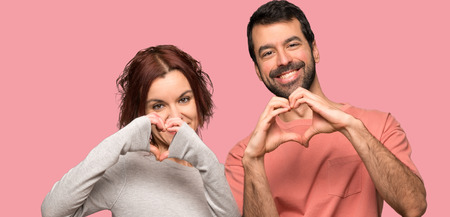 Couple in valentine day making a heart with hands over isolated pink background