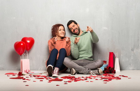 Couple in valentine day points finger at you with a confident expression