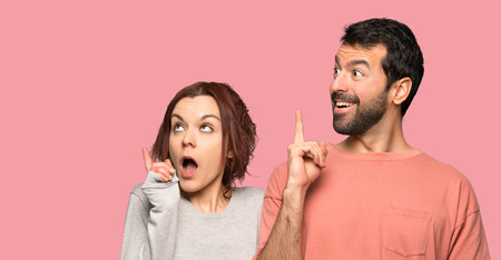 Couple in valentine day thinking an idea pointing the finger up over isolated pink background