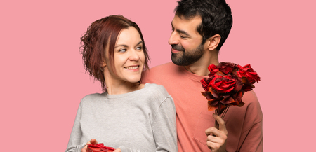 Couple in valentine day with flowers and gifts over isolated pink background