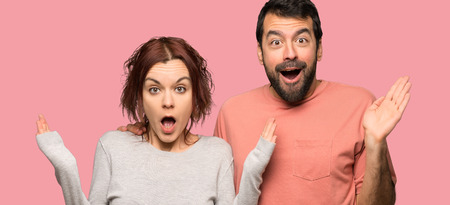 Couple in valentine day with surprise and shocked facial expression over isolated pink background
