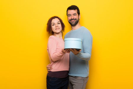 Couple in valentine day holding a gift in hands