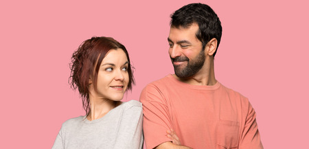 Couple in valentine day keeping the arms crossed looking at each other over isolated pink background
