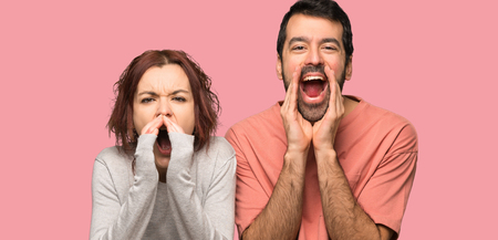 Couple in valentine day shouting and announcing something over isolated pink background