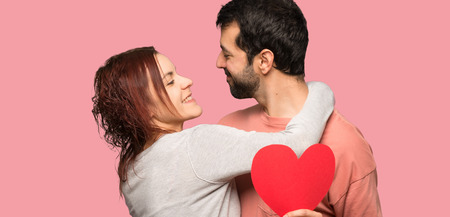 Couple in valentine day holding a heart symbol and kissing over isolated pink background Stock Photo