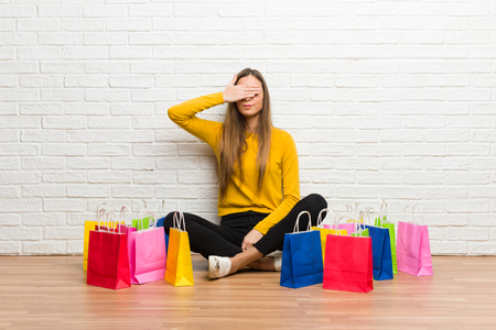 Young girl with lot of shopping bags covering eyes by hands. Do not want to see something Stock Photo