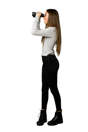 Full-length shot of young girl and looking in the distance with binoculars on isolated white background