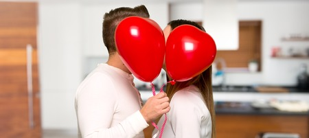 Couple in valentine day with balloons with heart shape in a house Standard-Bild