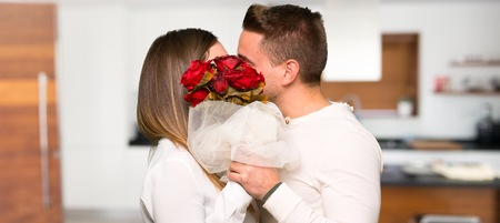 Couple in valentine day with flowers and kissing in a house