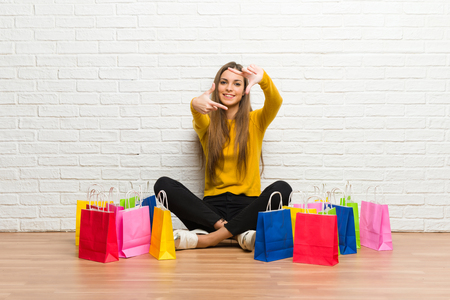 Young girl with lot of shopping bags focusing face. Framing symbol