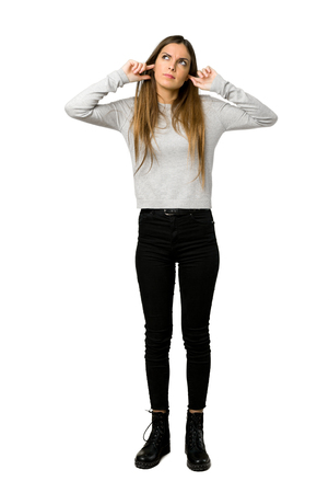 Full-length shot of young girl covering both ears with hands on isolated white background