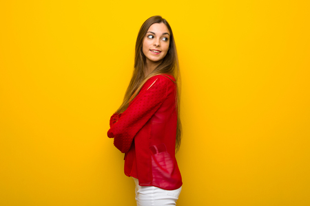 Young girl with red dress over yellow wall looking over the shoulder with a smile
