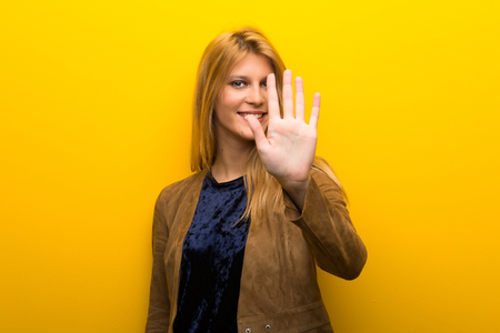 Blonde girl on vibrant yellow background counting five with fingers