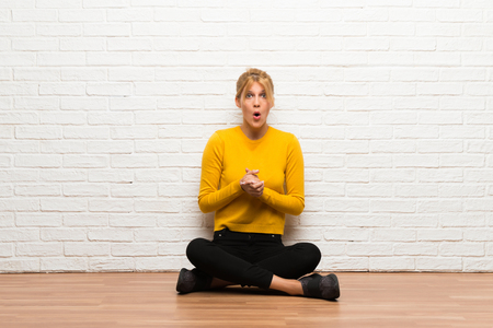 Young girl sitting on the floor with surprise and shocked facial expression Stok Fotoğraf