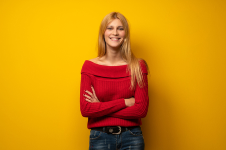 Blonde woman over yellow wall keeping the arms crossed in frontal position Reklamní fotografie