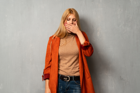 Woman over textured background yawning and covering wide open mouth with hand