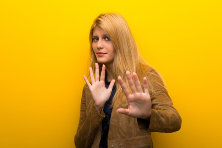 Blonde girl on vibrant yellow background is a little bit nervous and scared stretching hands to the front
